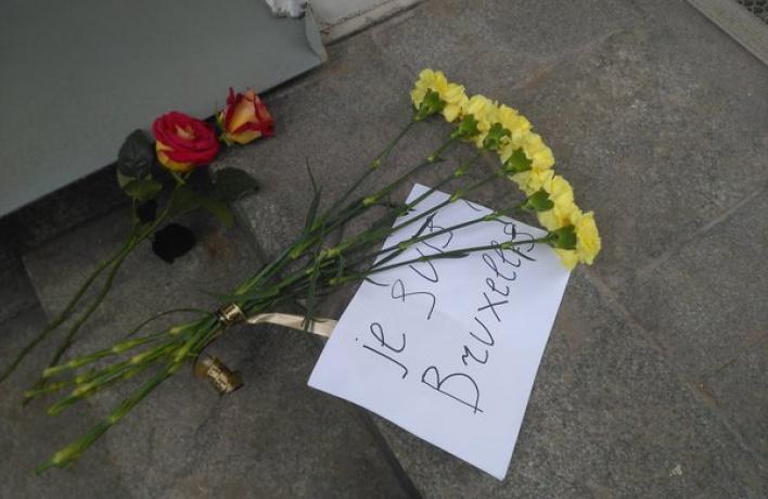 Люди несут цветы к зданию посольства Бельгии возле Арбата