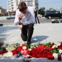 Люди несут цветы к посольству Франции